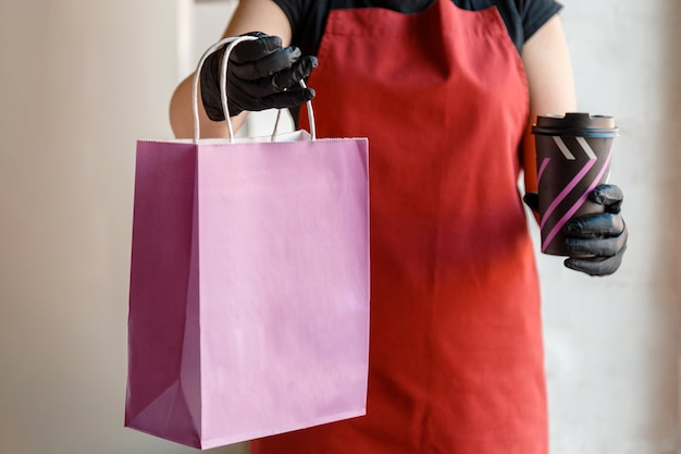 Essen zum mitnehmen lila papiertüte mock-up. kontaktlose lebensmittelzustellungssperre covid 19. lebensmittelbeutel, kaffeetassenpaket zum mitnehmen im restaurant zum mitnehmen. küchenarbeiter gibt bestellungen in handschuhen und maske aus.