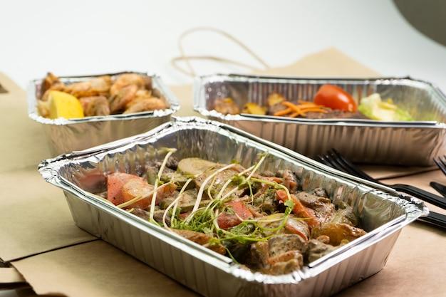 Essen zum mitnehmen, mittagessen in geschäftsboxen oder folienbehältern mitbringen
