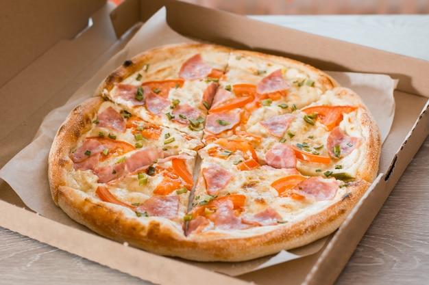 Essen zum mitnehmen. pizza in einem karton auf dem tisch in der küche. nahansicht
