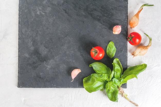 Essen . zutaten, gemüse und gewürze zum kochen, mittagessen. frische basilikumblätter, tomaten, knoblauch, zwiebeln, salz, pfeffer. auf einem weißen steintisch eine schiefertafel. ansicht von oben