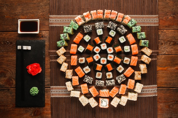 Essenskunst, tolles sushi-set. appetitliche auswahl an brötchen, buntes rundes ornament auf brauner strohmatte serviert, flach. luxuriöses japanisches restaurantmenüfoto.