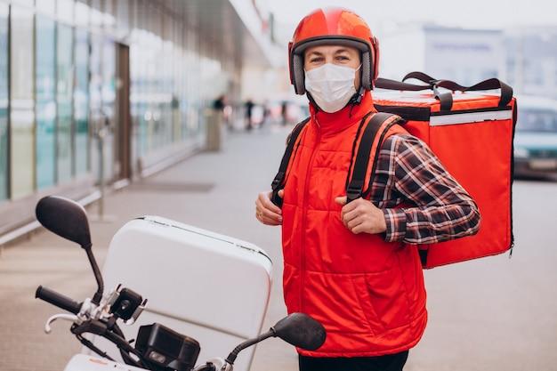 Essenslieferjunge fährt roller mit box mit essen und trägt maske