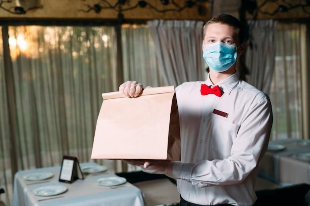 Essenslieferung aus dem restaurant. porträt eines kellners, der eine handwerkliche papiertüte für die lebensmittellieferung hält.