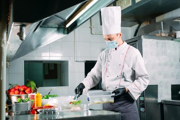 Essenslieferung im restaurant. der küchenchef bereitet das essen im restaurant zu und verpackt es in einweggeschirr.