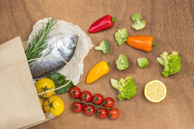 Essensset. papiertüte mit rohem fisch und gemüse.