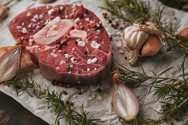 Essensset, zwiebeln, romero, rohes fleischsteak, salz, pfeffer, knoblauch, olivenöl, gabel, nahaufnahme