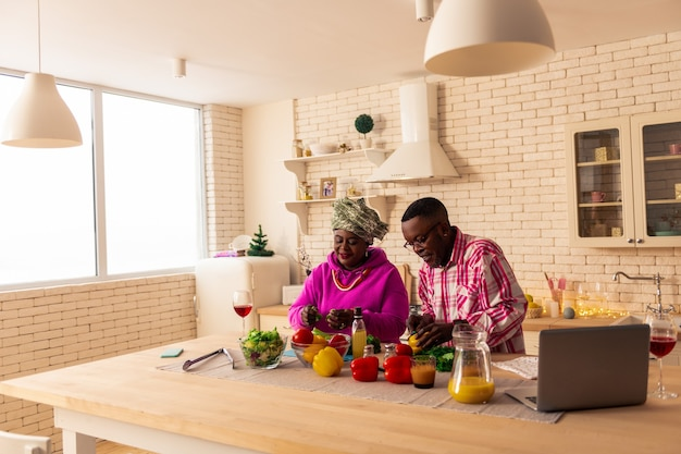 Essenszubereitung. fröhliches nettes paar, das über essen spricht, während es in der küche steht