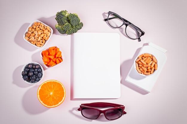 Essentielle vitamine und nahrungsergänzungsmittel, um die augen auf rosafarbenem hintergrund gesund zu halten. brillen, vitaminpillen, vitaminhaltige lebensmittel für gutes sehen mit text, gesunde augen, draufsicht, pastellrosa tischplatte