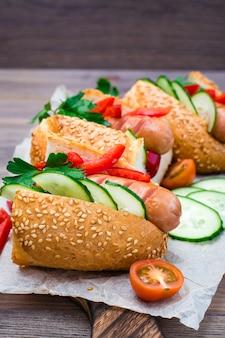 Essfertige hotdoge von gebratenen würsten, brötchen des indischen sesams und frischgemüse auf einem schneidebrett auf einem holztisch