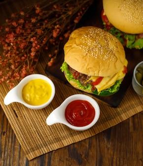 Essfertiger hamburger mit gelber und roter soße, von oben nach unten mit coupy-platz nehmen.