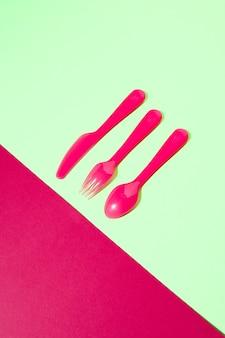 Essgeschirr aus kunststoff aus gabel, messer und löffel auf duotonem hintergrund mit exemplar. flach liegen.