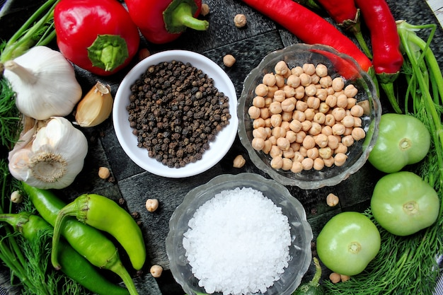 Essiggurken auf weißem holztisch mit den grünen und roten und paprikapfeffern, fenchel, salz, schwarzen pfefferkörnern, knoblauch, erbse, abschluss oben, gesundes konzept, draufsicht, ebenenlage