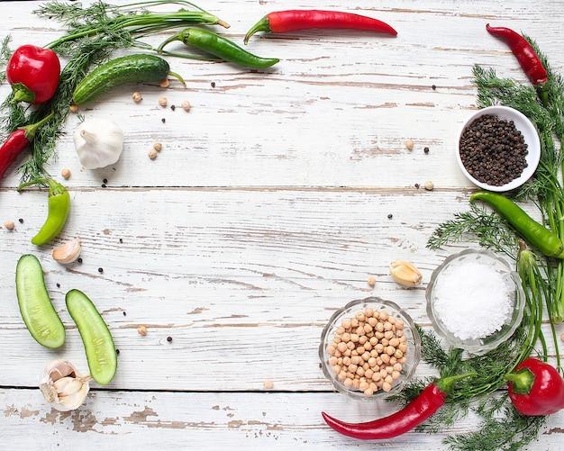 Essiggurkenhintergrund auf weißem holztisch mit den grünen und roten und paprikapfeffern, fenchel, salz, schwarzen pfefferkörnern, knoblauch, erbse, abschluss oben, gesundes konzept, draufsicht, ebenenlage
