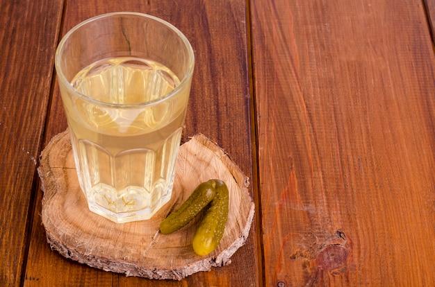 Essiggurkensaftglas, in essig eingelegte gurke auf holz