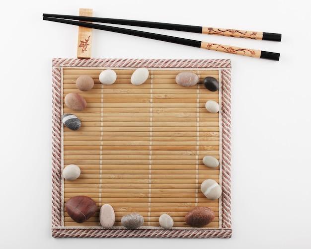 Essstäbchen befinden sich auf einem ständer neben einer bambusmatte, auf deren oberfläche dekorative steine