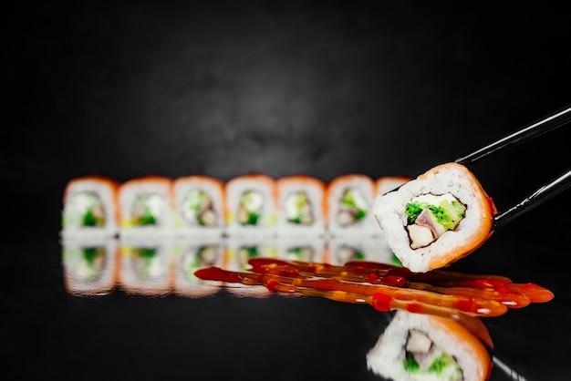 Essstäbchen, die den roten drachen der sushirolle halten, machten vom geräucherten lachs, nori