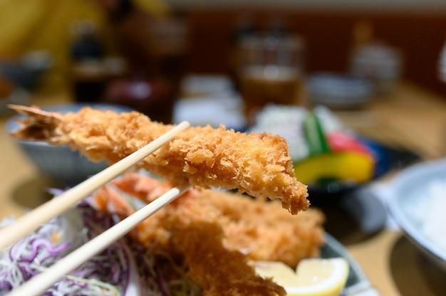 Essstäbchen, die eine knusprige tempuragarnele im restaurant klemmen
