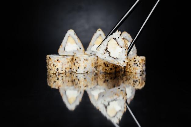 Essstäbchen, die sushirolle gemacht von nori, in essig eingelegtem reis, philadelphia-käse halten