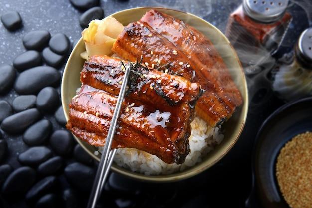 Essstäbchen halten japanischen aal gegrillt mit reisbecher.
