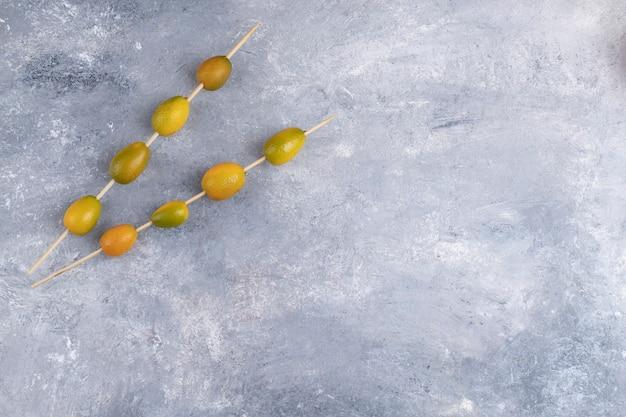 Essstäbchen mit frischen kumquats auf einem marmorhintergrund.