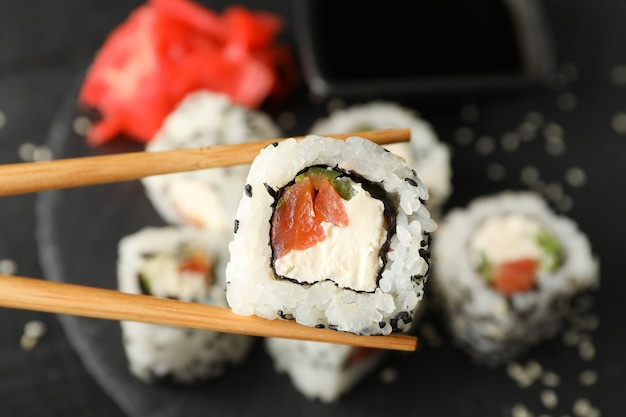 Essstäbchen mit leckerer sushi-rolle. japanisches essen