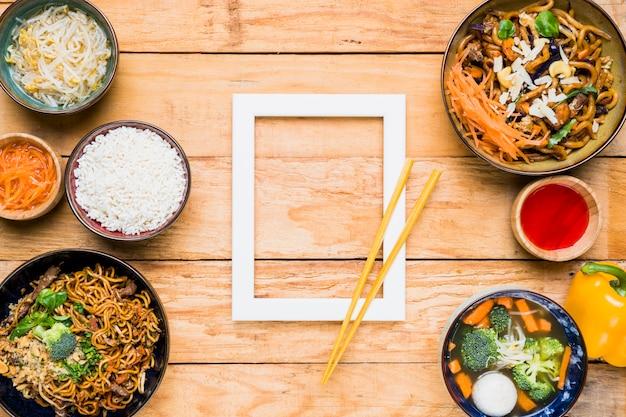 Essstäbchen über dem weißen grenzrahmen und dem thailändischen lebensmittel auf hölzernem schreibtisch