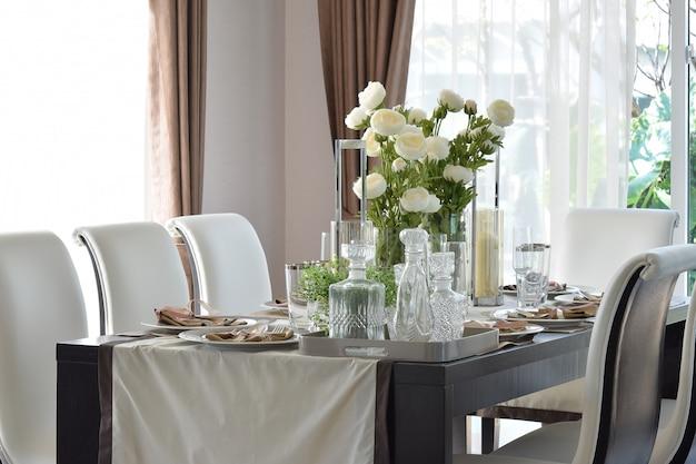 Esstisch aus holz und bequeme stühle in einem modernen zuhause mit elegantem gedeck