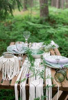 Esstisch des boho-arthochzeitsempfangs mit makrameetischdecke, dekoration auf einem rustikalen holztisch
