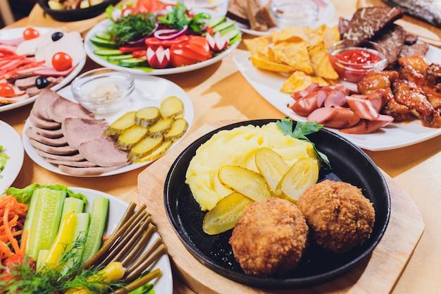 Esstisch mit einer vielzahl von snacks und salaten. lachs, oliven, wein, gemüse, gegrillter fisch toast.