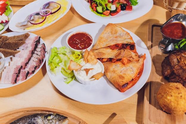 Esstisch mit einer vielzahl von snacks und salaten
