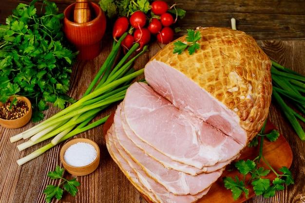 Esstisch mit ganzem gebackenem und geschnittenem schinken, gemüse und gewürzen.