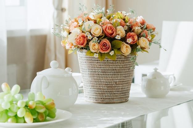 Esstisch mit geschirr für tee, trauben, blumen