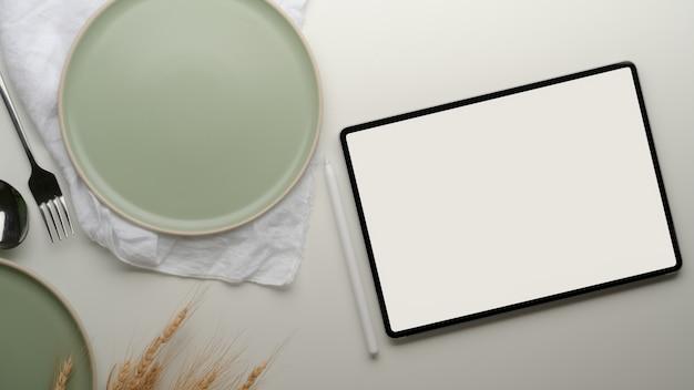 Esstisch mit tablette, türkisfarbenen keramikplatten, serviette und goldenem weizen auf dem tisch dekoriert