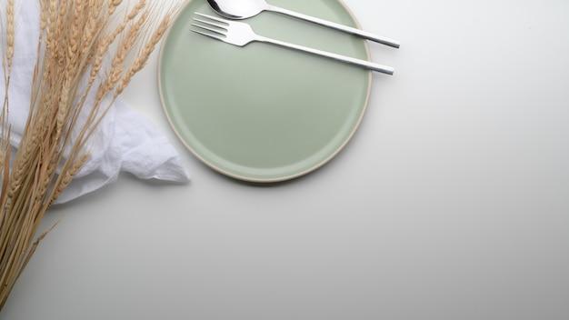 Esstisch mit türkisfarbenem teller, besteck, serviette, ablagefläche und goldenem weizen auf dem tisch