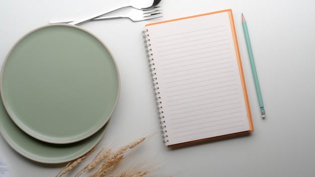 Esstisch mit türkisfarbenen keramikplatten, besteck, leerem notizbuch, bleistift und goldenem weizen auf dem tisch dekoriert