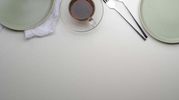 Esstisch mit türkisfarbenen tellern, besteck, teetasse, serviette und ablagefläche
