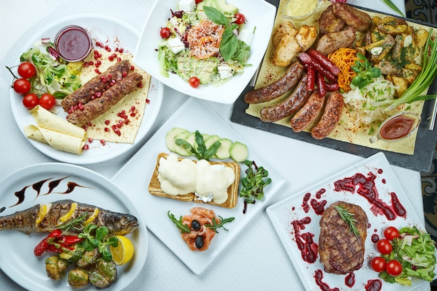 Esstisch mit verschiedenen gerichten - lula kebab, hühnchen- und schweinefleischgrill, gegrillte würste, ribeye-steak vom rind, toast mit pochierten eiern, gegrillter wolfsbarsch. draufsicht