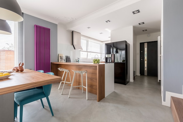 Esszimmer, küche und eingang in modernem einfamilienhaus mit minimalistischem grauem design, farbenfrohen akzenten und holzmöbeln