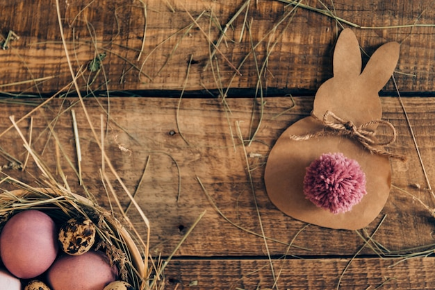 Ester hase. draufsicht auf farbige ostereier in schüssel mit heu und osterhase aus braunem papier, die auf rustikalem holztisch liegen lying