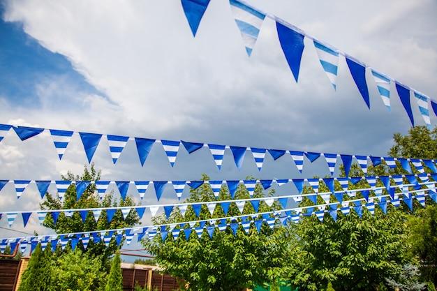 Estival-flaggenlinie mit blauem himmel herein. flagge, die zum spaß am blauen himmel-fiestaparteiereignis hängt