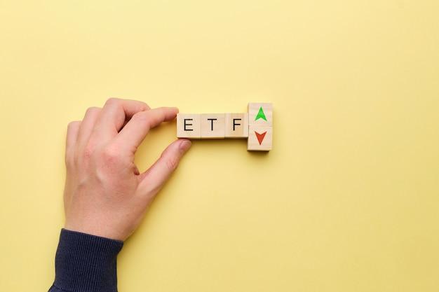 Etf-konzept mit aufwärts- und abwärtspfeilen auf gelbem hintergrund.