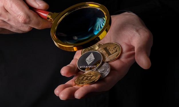 Ethereum silber- und goldmünzen der kryptowährung in männlicher handfläche über schwarzem hintergrund, nahaufnahme