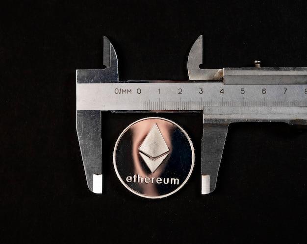 Ethereum-silbermünze auf schwarzem hintergrund mit risikomesswerkzeug.