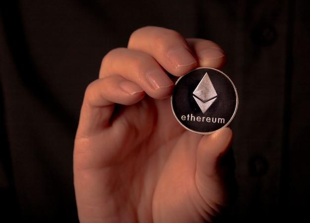 Ethereum silberne kryptomünze in männlicher hand über schwarzem hintergrund eth oder etherum