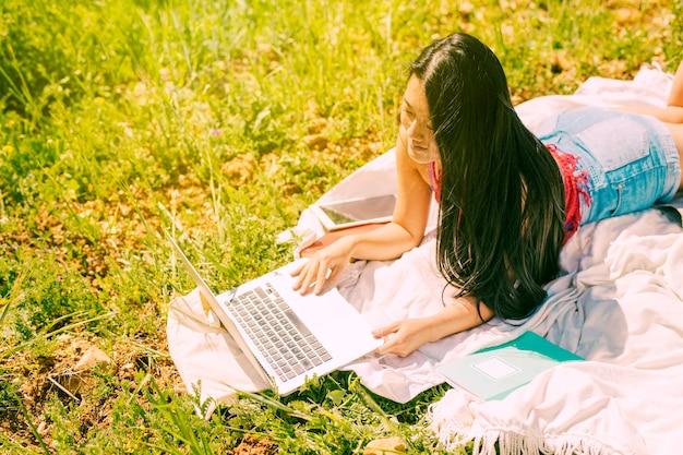 Ethnische brunettefrau, die laptop in der lichtung untersucht