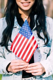 Ethnische frau, die amerikanische flagge hält