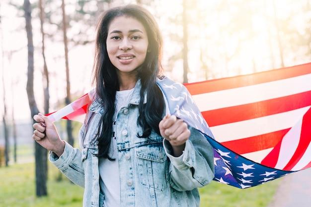 Ethnische frau mit amerikanischer flagge auf schultern