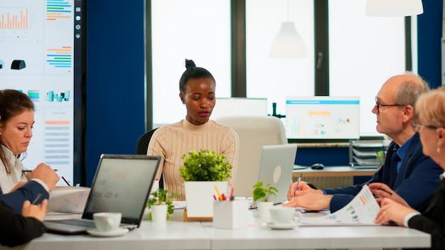 Ethnische geschäftsführung, die einen geschäftsplan plant, der in der sitzung des sitzungssaals sitzt. vielfältige teamarbeit zur diskussion der finanzstrategie für ein neues start-up-unternehmen, das im brainstorming-büro arbeitet.