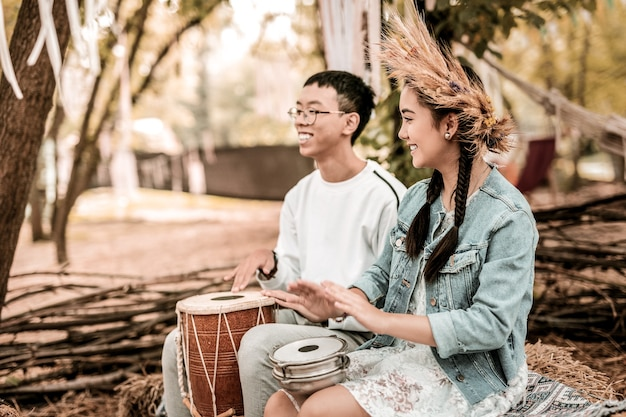 Ethnische musik. schönes langhaariges mädchen, das lächeln auf ihrem gesicht hält, während trommel benutzt