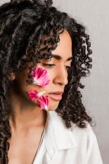 Ethnische romantische frau mit blumenblumenblättern auf gesicht